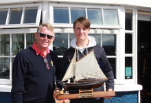 1st Radial receiving the perpetual trophy from Brian Jones, Rear Admiral Dinghies