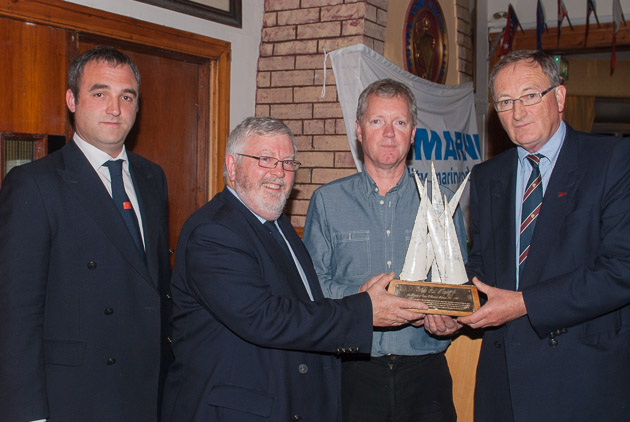 Mark Ivers, on behalf of the O'Donovan family, presenting the trophy to Kevin Lane. Also in pic Admiral Pat Lyons and Rear Admiral Keelboats Kieran O'Connell. Picture Robert Bateman