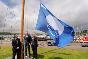 Senator Jerry Buttimer hoists the 2017 Blue Flag, watched by Ian Diamond, An Taisce (left) & Gavin Deane, General Manager Royal Cork Yacht Club (centre)